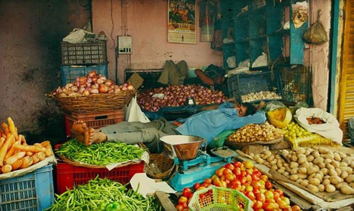 man sleeping at a market stall in Varanasi, India