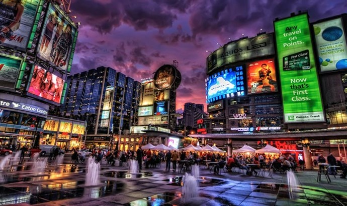 Yonge & Dundas Square in downtown Toronto lit up at dusk with the bright lights of the billboards while rain puddles can be seen in the foreground