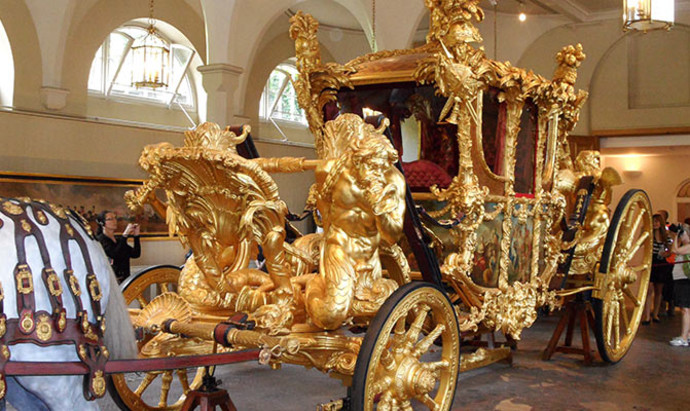 Ornate royal golden carriage in the Royal Mews, London